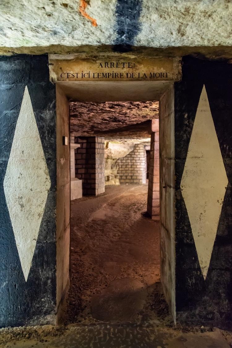 """Porte d'entrée des catacombes de Paris, France. Texte au sens français : """"Arrêtez, voici l'empire de la mort"""""""