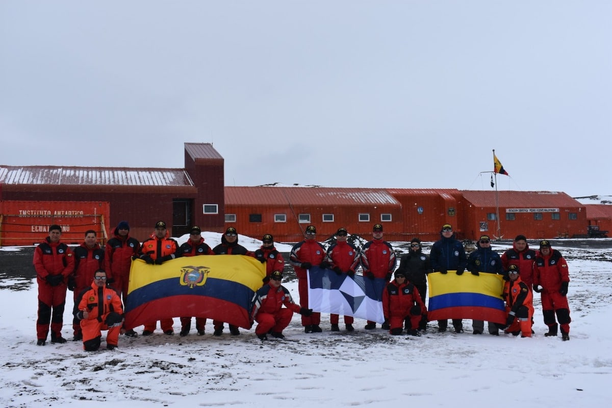 Members of Ecuador and Colombia's National Antarctic Programs with True South and their national flags at Maldonado Base, Antarctica