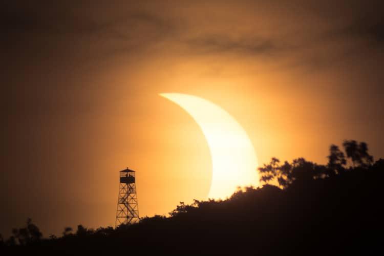 Éclipse solaire à côté d'une tour