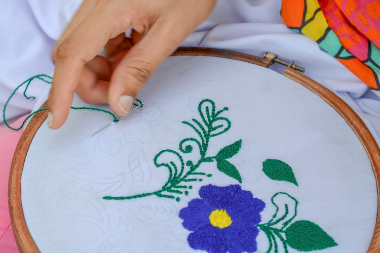 Person Stitching a Flower in an Embroidery Hoop