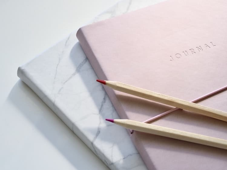 Journals Stacked on Top of Each Other With Pencils on Top