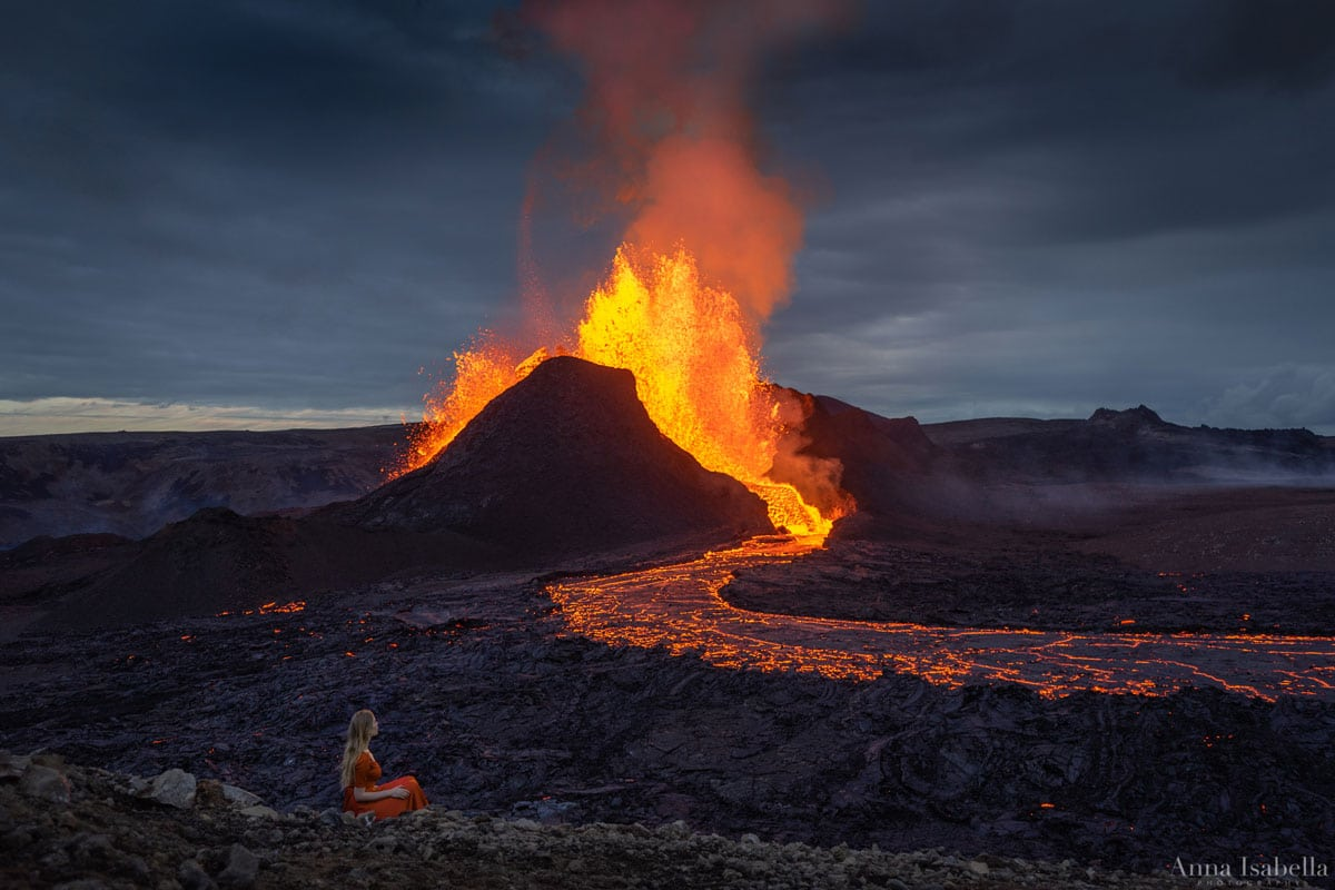 Fagradalsfjall Volcano Erupting with Woman Seated in the Foreground