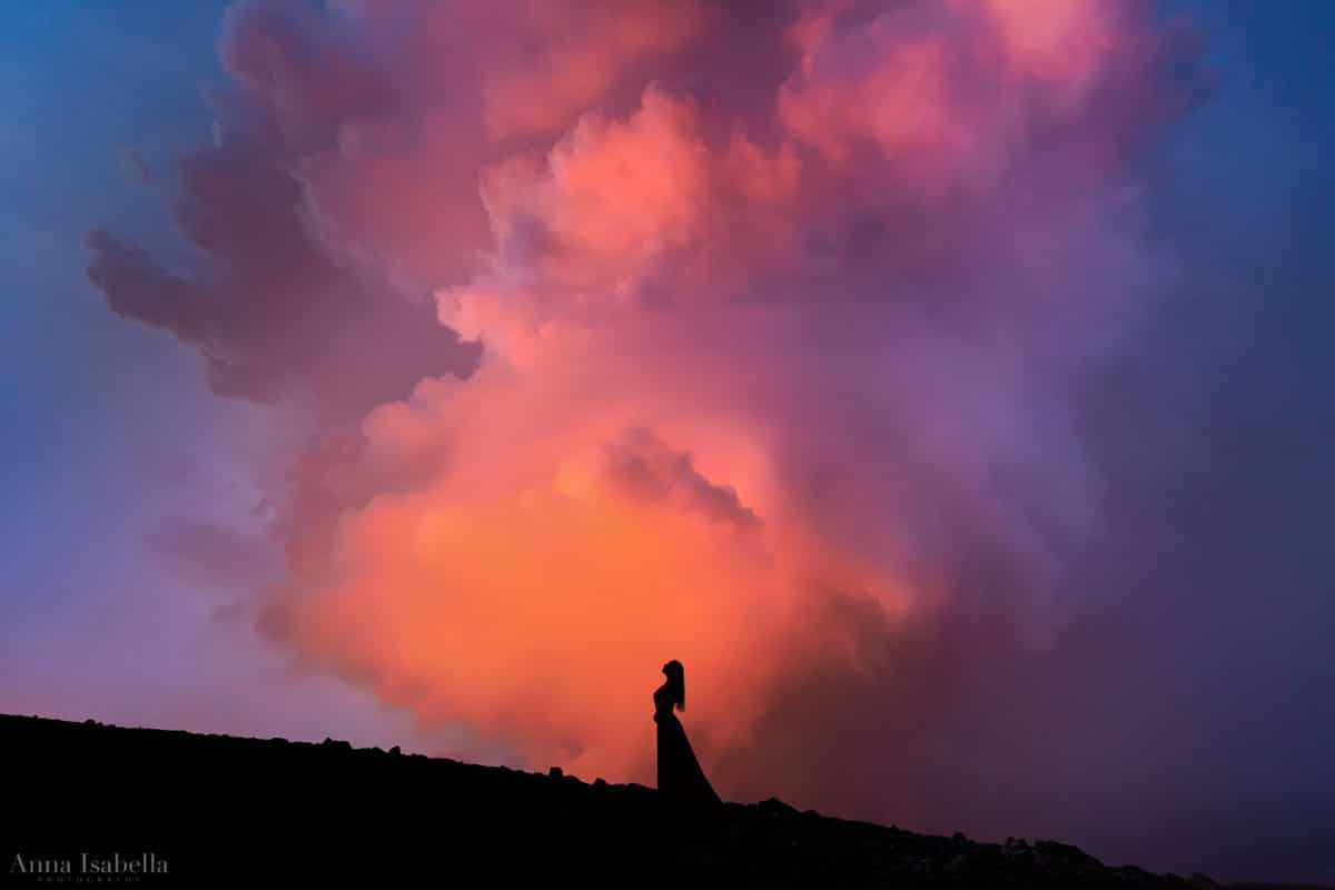 Woman Posing in front of Smoke From Erupting Volcano