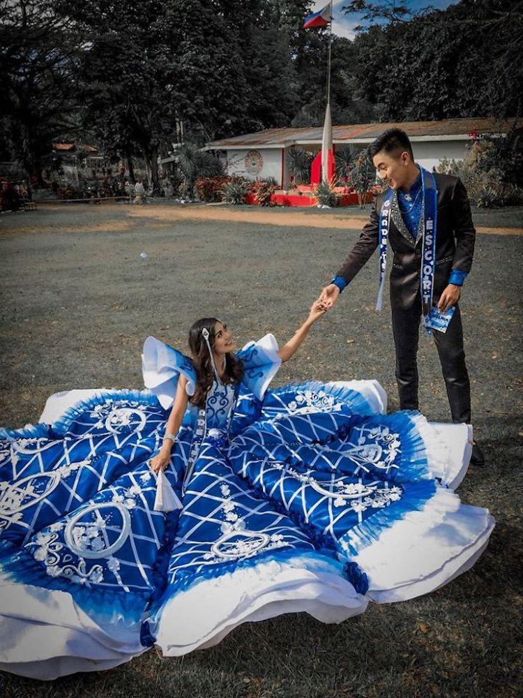 joven con vestido de graduación azul hecho a mano sentada en el suelo toma mano de un joven