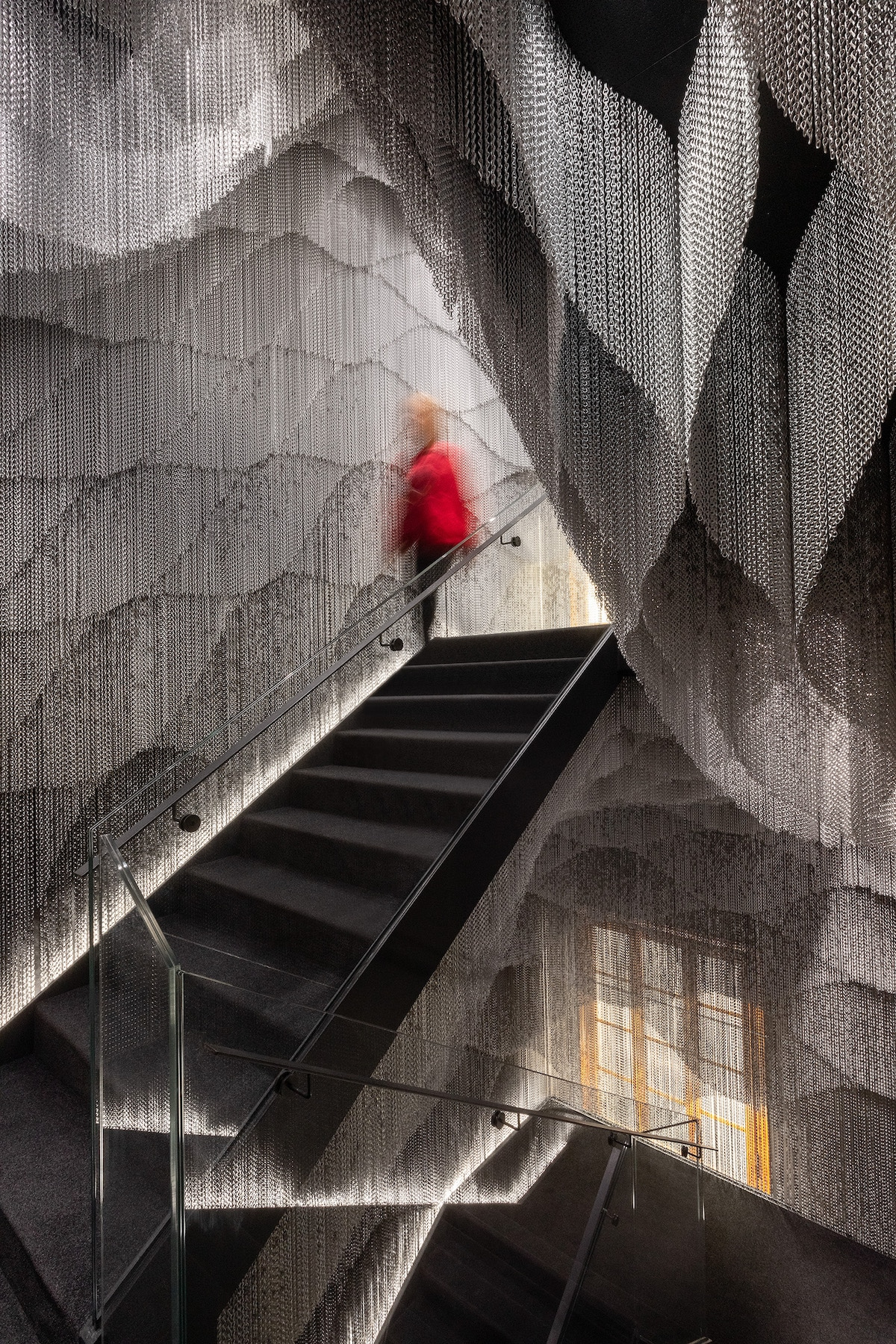 Person Passing Inside Kengo Kuma Aluminum Chain Staircase in Gaudí's Casa Batlló, Captured by Jordi Anguera