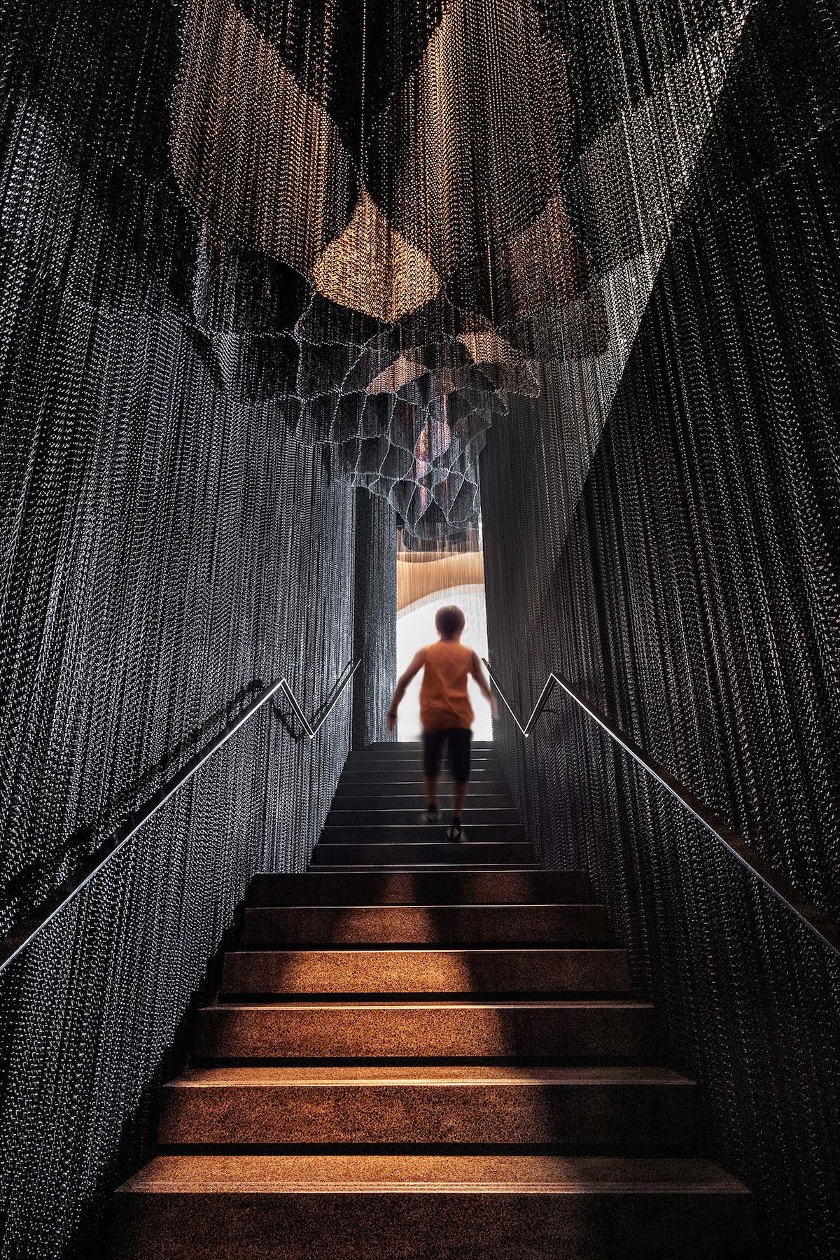Person Walking Up Kengo Kuma Aluminum Chain Staircase in Gaudí's Casa Batlló, Captured by Jordi Anguera