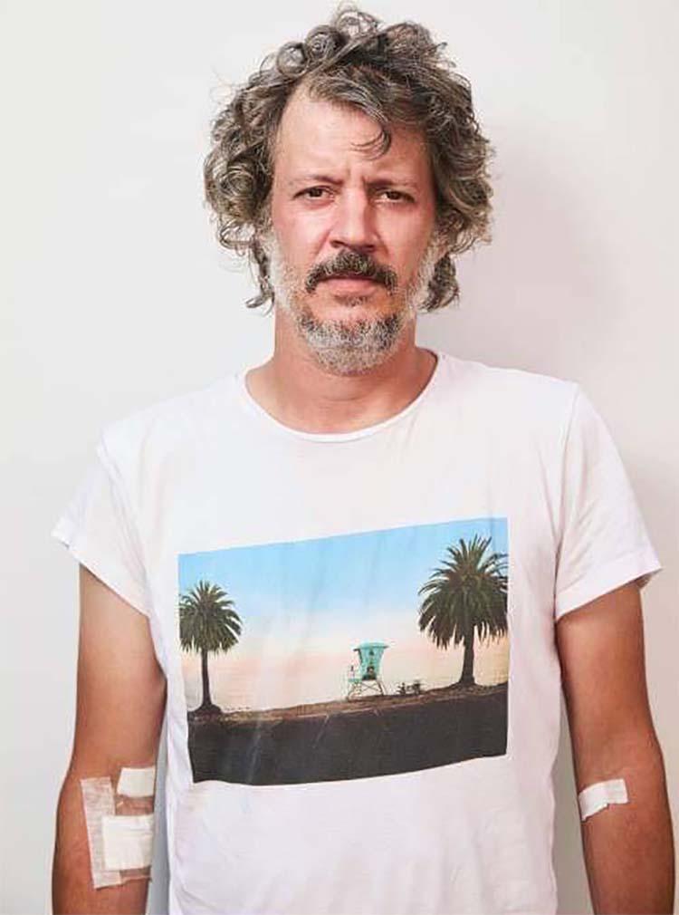 hombre con cabello rizado con camiseta blanca con palmera