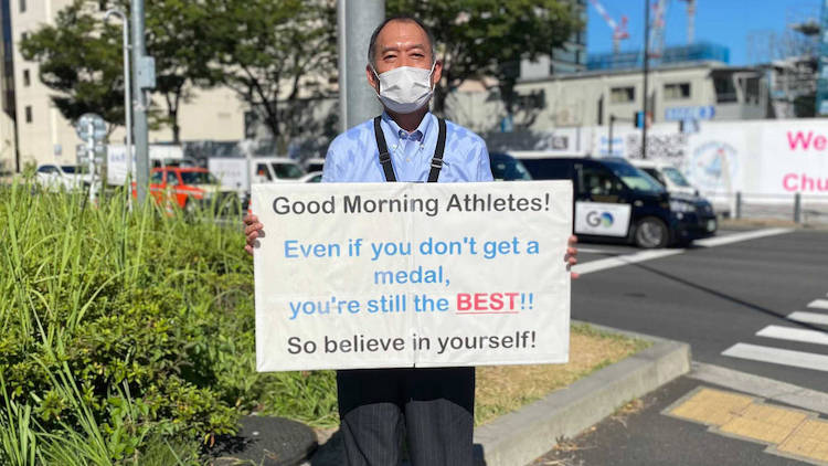 Man Holds Daily Motivational Posters for Athletes at the Tokyo Olympics