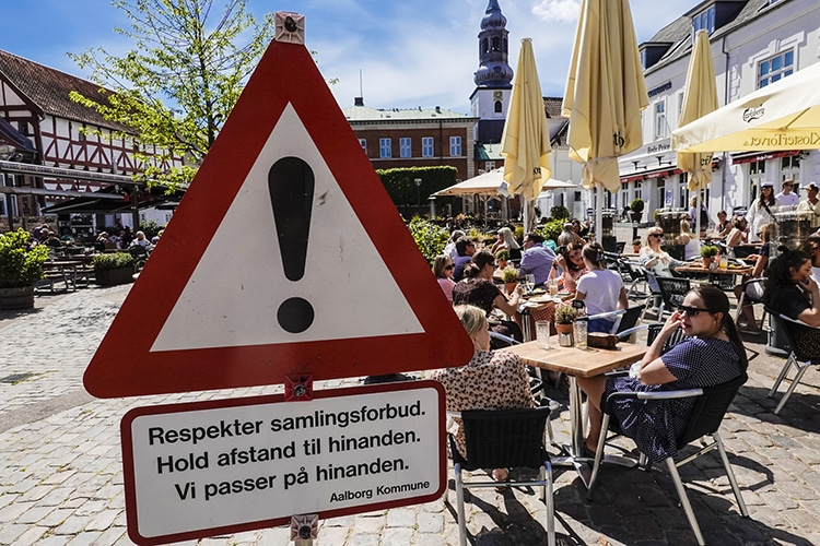 A sign in Aalborg, Denmark advertises social distancing measures.
