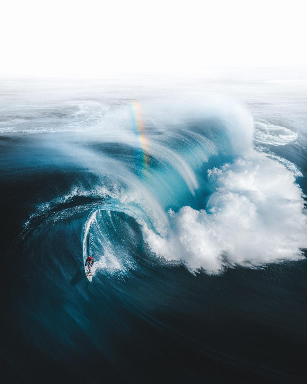 Surfer sur les vagues en Australie sous un arc-en-ciel