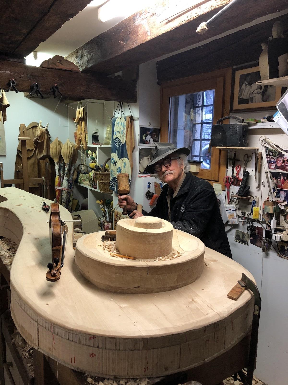 Livio de March Working on Giant Violin in His Studio