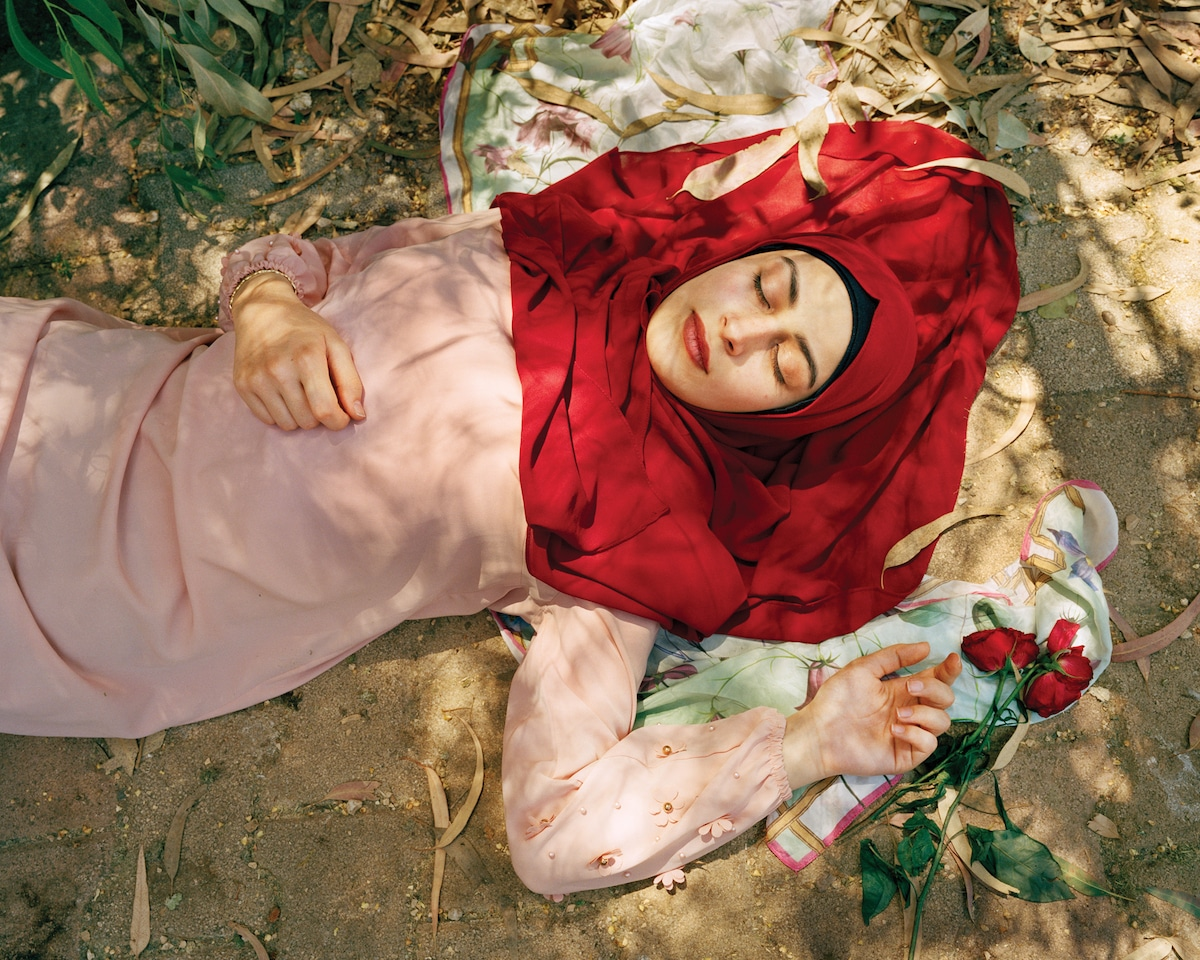 Woman with Red Headscarf Laying on the Ground