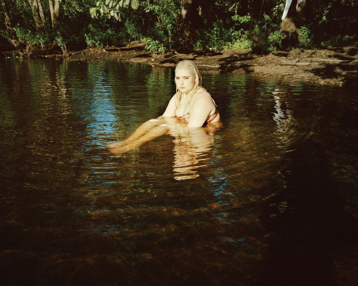 Young Woman Sitting in Shallow Water