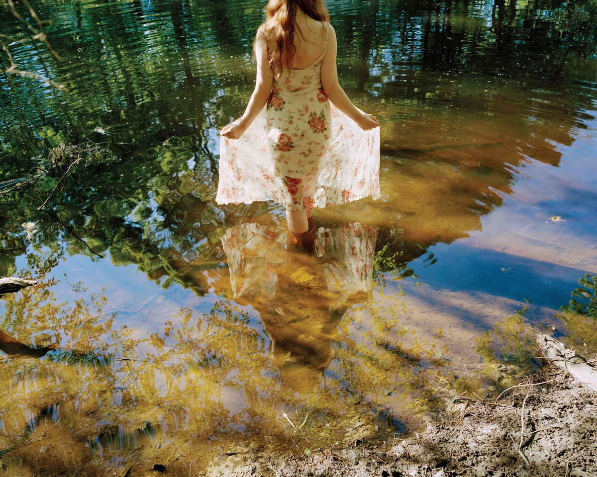 Photo of a Young Woman Wading into Water