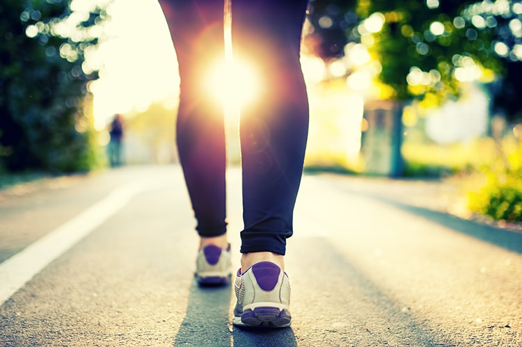 Close-up of woman athlete feet and shoes while running in park. Walking for health.