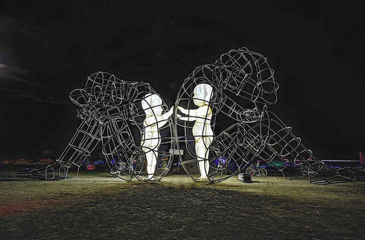 burning man sculpture reveals inner child glowing within giant wire