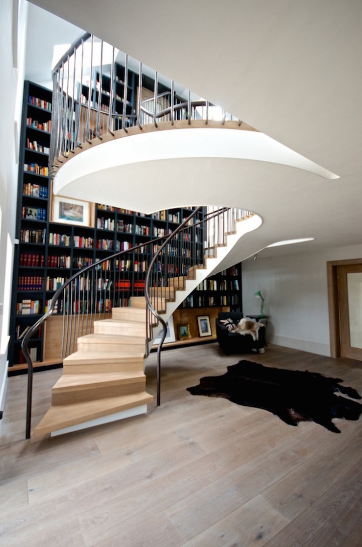 Spiral Staircase Effortlessly Flows by Floor-to-Ceiling Bookcase