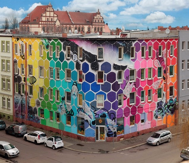 Giant rainbow honeycomb mural takes over a building in for Construction mural